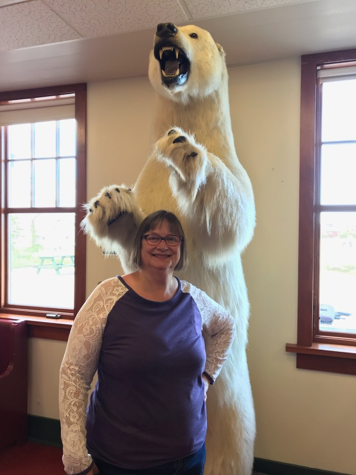 A photo of Laurie Wood standing next to a polar bear in Churchill, Manitoba, Canada. From a July 2019 reserach trip.